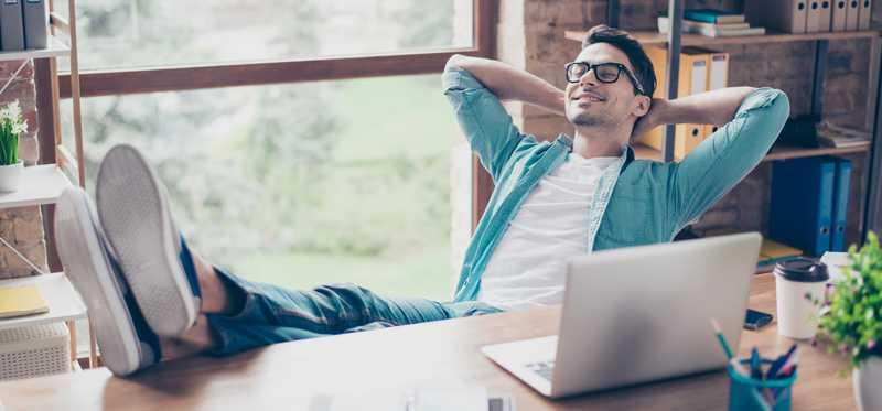 Man relaxing with feet up on desk and hands behind head.
