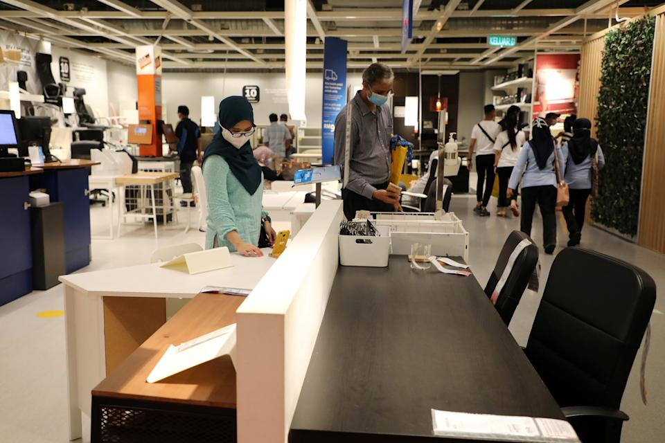 Customers wearing protective masks shop for office furniture at IKEA. Photo: Lim Huey Teng/Reuters