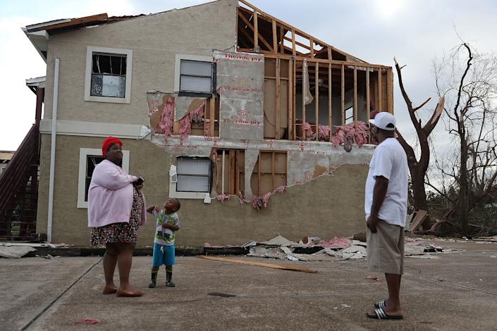 Comeasha Stanley, Ramari Stanley and Terrell Atkinson stand near a heavily damaged apartment in Panama City.