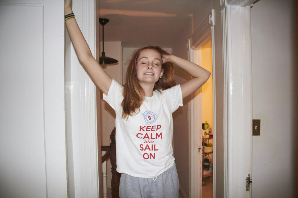 Shot of a teenage girl standing in a hallway of a home. She has long red hair. She has one arm up on the wall and the other hand is in her hair. She has her head thrown back and her eyes are closed and she is smiling. She is wearing a t shirt with a funny saying on it. She looks like she is sleepy. She seems like she could be just waking up or going to sleep.