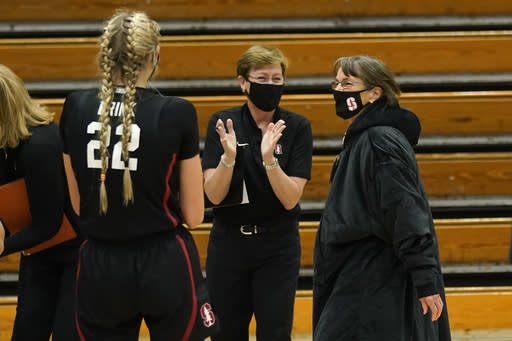 Stanford coach Tara VanDerveer, right, receives congratulation from Eileen Roche, center, Stanford's director of women's basketball operations after defeating Pacific 104-61 in an NCAA college basketball game in Stockton, Calif., Tuesday, Dec. 15, 2020. With the win, VanDerveer becomes the winningest coach in women's basketball history passing the late Pat Summitt with her 1,099 victories. (AP Photo/Rich Pedroncelli)