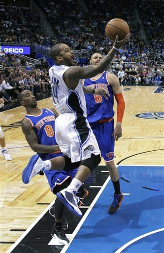 Orlando Magic's Jameer Nelson, center, gets around New York Knicks' J.R. Smith (8) and Tyson Chandler (6) for a shot during the first half of an NBA basketball game, Saturday, Jan. 5, 2013, in Orlando, Fla. (AP Photo/John Raoux)