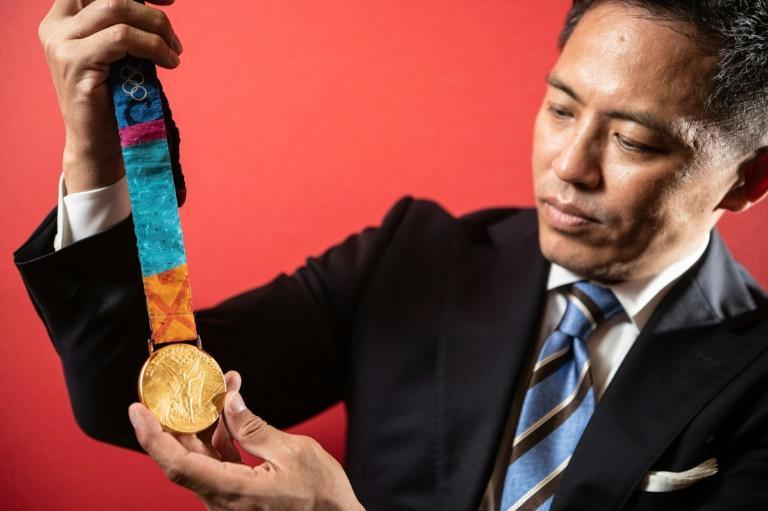 Gold standard: Japan's Tadahiro Nomura shows his 2004 Athens Olympics gold medal, his third of a unqiue judo hat-trick that can be matched by France's Teddy Riner in Tokyo