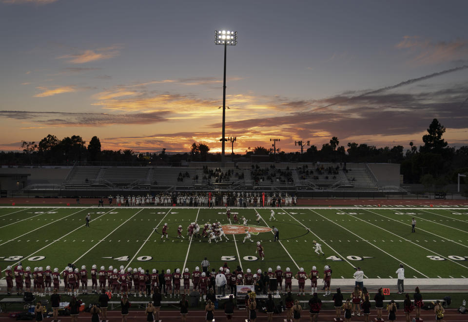 The sun sets behind the stadium during a high school football game between El Modena and El Dorado in Orange, Calif., Friday, March 19, 2021. The team recently played its first football game in a year as more California counties ease coronavirus restrictions and life in the nation's most populous state inches back to normalcy. (AP Photo/Jae C. Hong)