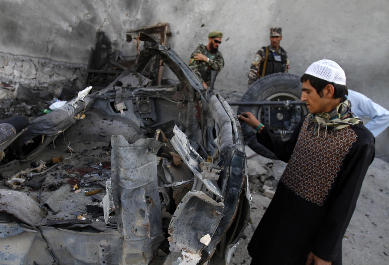 An Afghan man examines the remains of a car after three suicide bombers were killed before they reached Jalalabad airport, which security forces say was their target, in Jalalabad, east of Kabul, Afghanistan on Sunday, April 15, 2012. The Taliban launched a series of coordinated attacks on at least seven sites across the Afghan capital on Sunday, targeting NATO headquarters, the parliament and diplomatic residences. Militants also launched near-simultaneous assaults in three other eastern cities. (AP Phot/Rahmat Gul)