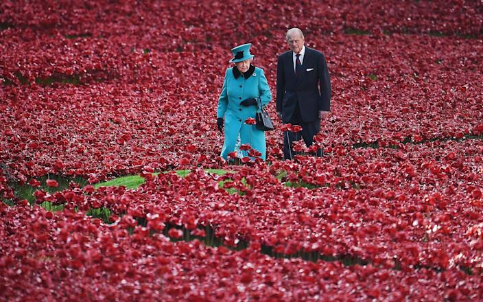 The Queen and the late Prince Philip, Duke of Edinburgh walking among ceramic red poppies planted in memory of the British and Commonwealth dead from WWI in the moat at the Tower of London on October 16, 2014 - Andy Rain/PA-EFE/Shutterstock