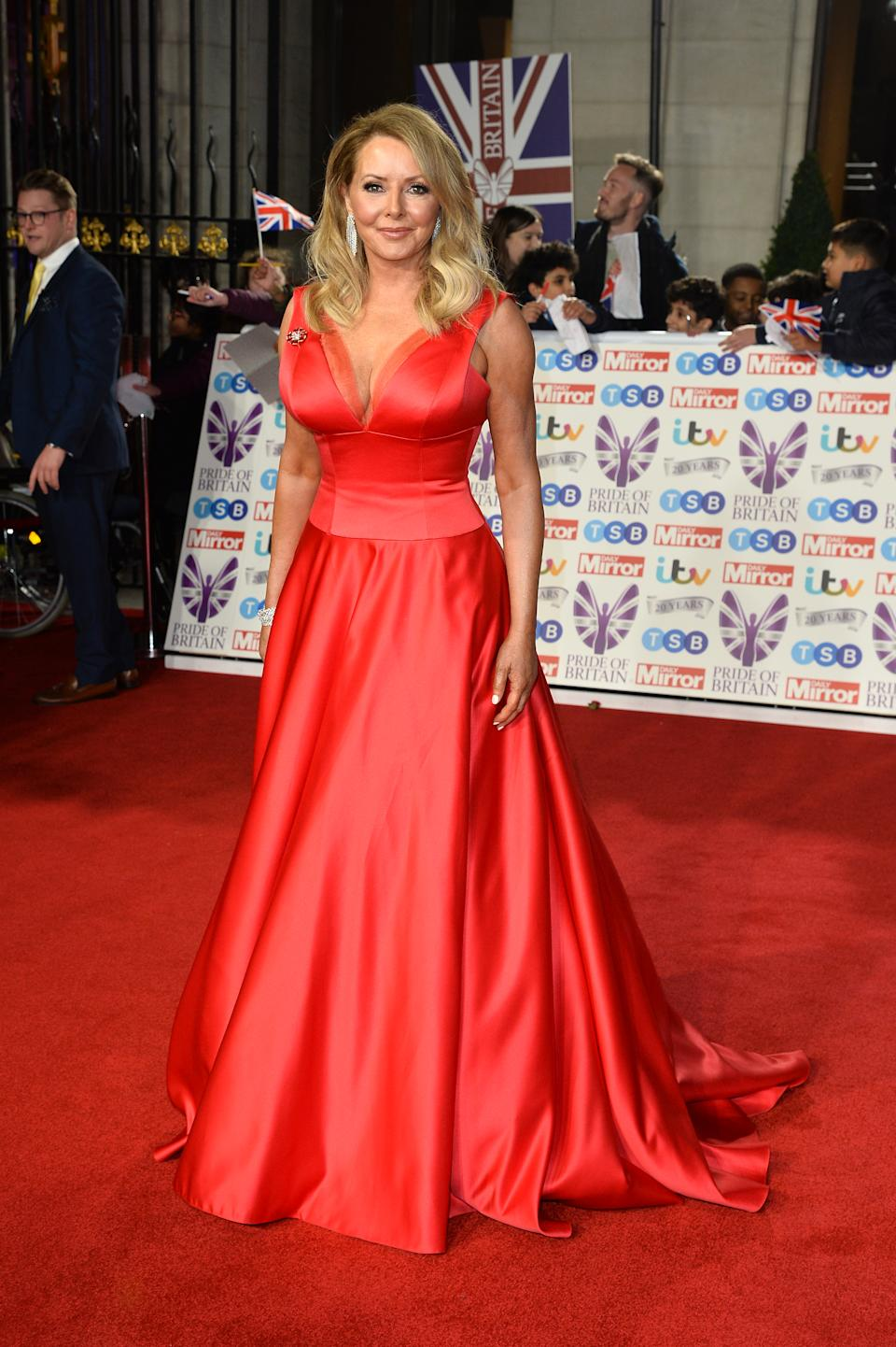 Host of the evening Carol Vorderman wore a plunging red satin gown. [Photo: Getty]