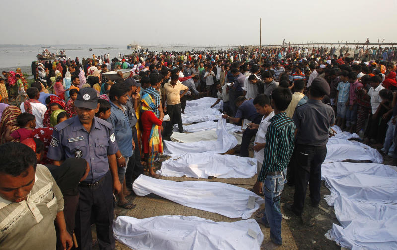 Bangladeshis crowd around the dead bodies of victims of a ferry that capsized in the Meghna River in Munshiganj district, about 20 miles (32 kilometers) south of Dhaka, Bangladesh, Wednesday, March 14, 2012. The ferry, carrying about 200 people, collided with a cargo boat and capsized in the darkness of Tuesday morning, sending hundreds of people into the Meghna River, just south of the capital, Dhaka. The death toll rose to 110 while dozens of passengers still remain missing. (AP Photo/Pavel Rahman)