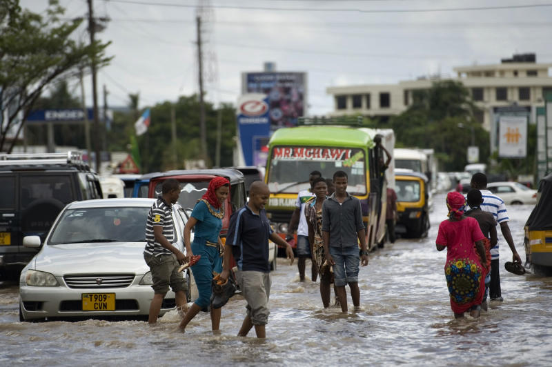 Pedestrians cross the flooded Old Bagamoyo Road in the Mikocheni area of Dar es Salaam, Tanzania, on April 12, 2014