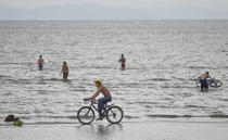 A man rides his bicycle along the shores of Cocibolca Lake, also known as Nicaragua Lake, in Granada, Nicaragua, Friday, June 7, 2013. A concession to build a canal across Nicaragua linking the Pacific Ocean and Caribbean Sea, which would go through the waters of Lake Nicaragua, will be awarded to a Chinese company, the National Assembly president said Wednesday. (AP Photo/Esteban Felix)