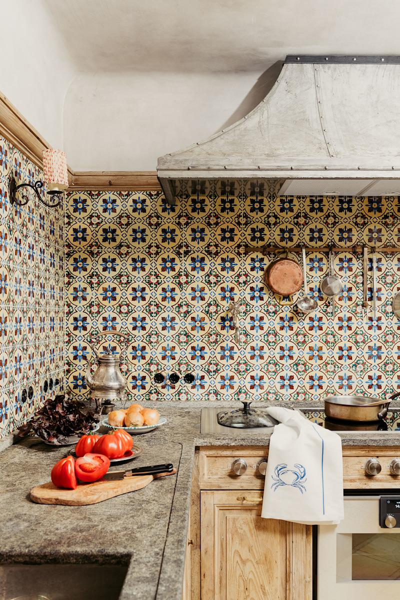 A custom iron hood by Studio Peregalli mixes with Portuguese tiles in the kitchen. Peperino marble countertops; Fir cabinetry.