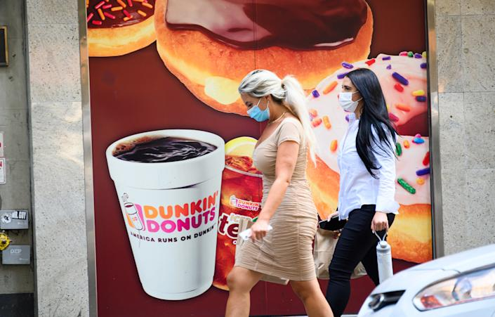 People wear protective face masks outside Dunkin' Donuts on the Upper West Side as the city continues Phase 4 of re-opening following restrictions imposed to slow the spread of coronavirus on July 28, 2020 in New York City. (Noam Galai/Getty Images)