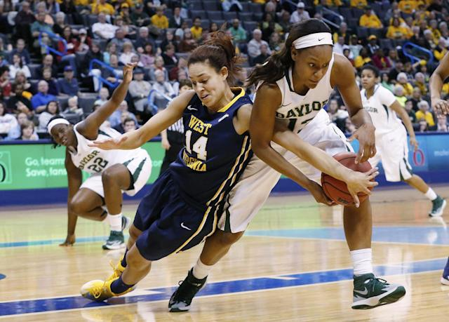 West Virginia forward Jess Harlee (14) reaches in to try and knock the ball away from Baylor forward Nina Davis (13) in the first half of an NCAA college basketball game in the finals of the Big 12 Conference women's college tournament in Oklahoma City, Monday, March 10, 2014. (AP Photo/Sue Ogrocki)
