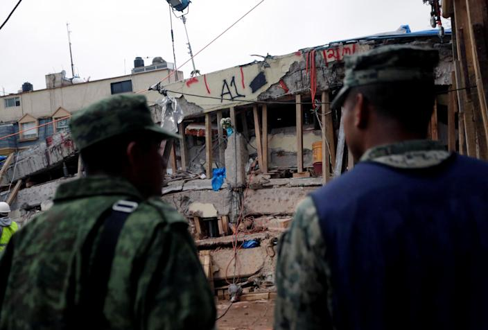 <p>Soldiers stand near parts of a collapsed school building during a search for students at the Enrique Rebsamen school after an earthquake in Mexico City, Mexico, Sept. 21, 2017. (Photo: Daniel Becerril/Reuters) </p>