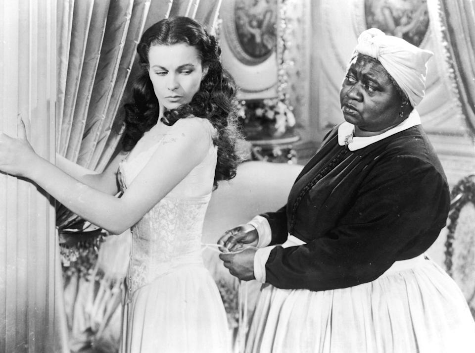 1939:  British actor Vivien Leigh (1913 - 1967) holds on to a pillar as American actor Hattie McDaniel (1895 - 1952) tightens her corset in a still from the film, 'Gone with the Wind,' directed by Victor Fleming.  (Photo by MGM Studios/Getty Images)