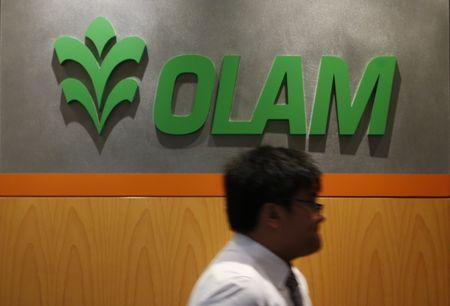 A man walks past a logo of Olam International Limited at its office in Singapore November 29, 2012. REUTERS/Edgar Su/Files