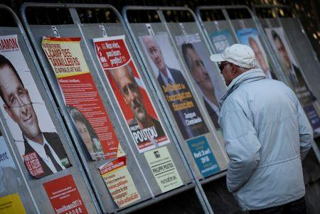 A man looks at campaign posters of the 11th candidates who run in the 2017 French presidential election in Enghien-les-Bains