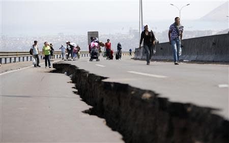 People walk next to a crack along a damaged road leading to Alto Hospicio commune, after a series of aftershocks, in the northern port of Iquique