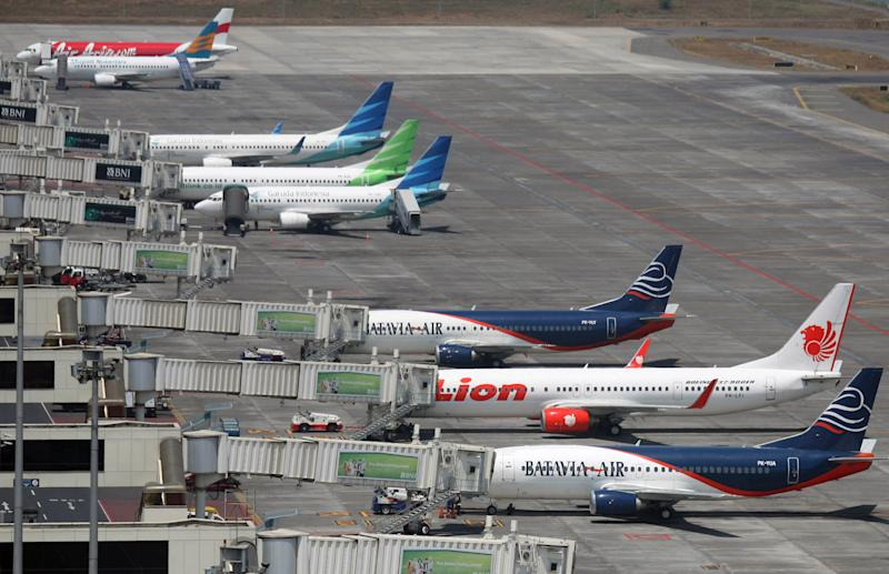 In this Tuesday, Sept. 25, 2012 photo, budget airlines' passenger jets, Malaysia's AirAsia, top, Indonesia's Badavia Air, third from bottom and bottom, and Indonesia's Lion Air, second bottom, are parked on the tarmac with Indonesian planes of domestic airline Merpati Nusantara, second top, and the flagship carrier Garuda Indonesia at Juanda International Airport in Surabaya, East Java, Indonesia. From almost none a decade ago, Asia now has more than 50 low cost carriers. The fast growth of no-frills airlines underline surging demand in the region for affordable air travel. (AP Photo/Trisnadi)