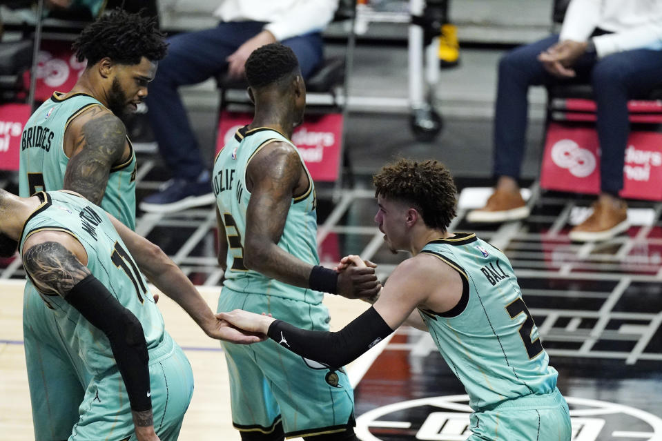 Charlotte Hornets guard LaMelo Ball, right, is helped up by teammates forward Cody Martin, left, forward Miles Bridges, second from left, and guard Terry Rozier after being fouled while shooting late in the first half of an NBA basketball game against the Los Angeles Clippers, Saturday, March 20, 2021, in Los Angeles. Ball is expected to miss the rest of the season due to a broken right wrist, according to a person familiar with the situation. The person spoke to The Associated Press on Sunday on condition of anonymity because the team has not made the status of his injury public. He appeared to be hurt after a fall in the Hornets' 125-98 loss to the Clippers in Los Angeles on Saturday. (AP Photo/Mark J. Terrill)