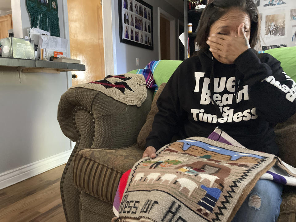 Seraphine Warren cries as she talks about her missing aunt, Navajo rug weaver Ella Mae Begay, while holding a rug made by Begay at her home in Tooele, Utah, on Sept. 23, 2021. Begay, 62, disappeared in June, one of thousands of missing Indigenous women across the U.S. The extensive coverage of the Gabby Petito case is renewing calls to also shine a spotlight on missing people of color. (AP Photo/Lindsay Whitehurst)