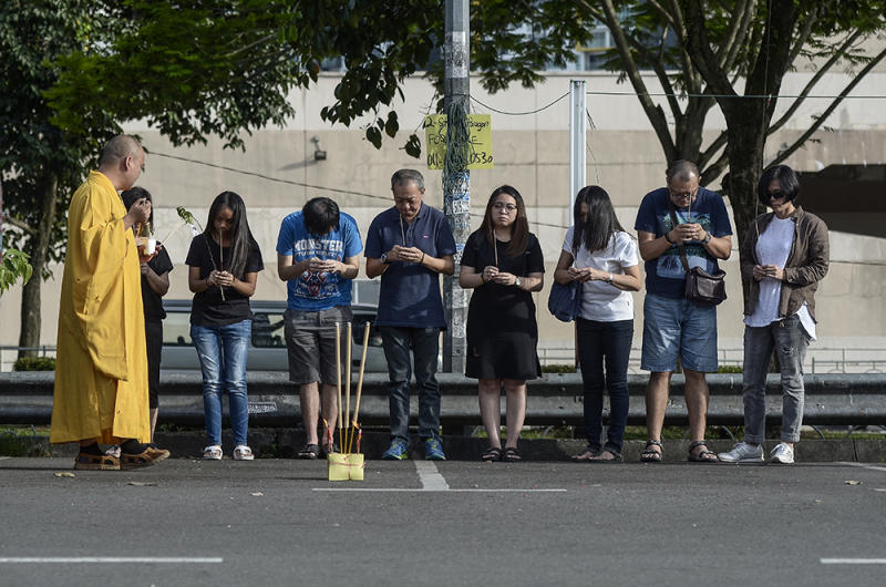 Family members of the hit and run accident victims hold prayers at the location of the incident in Serdang November 19, 2018. — Picture by Miera Zulyana