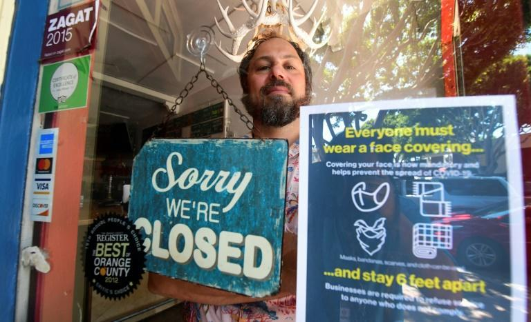 Gabriel Gordon stands behind the glass entrance door to his restaurant Beachwood BBQ, in Seal Beach, Californian, which he has been forced to permanently shut down because of the coronavirus pandemic