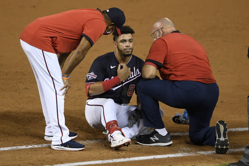 Washington Nationals' Luis Garcia, center, is tended to after he was injured reaching first on a fielding error by New York Mets first baseman Pete Alonso during the third inning of the second baseball game of a doubleheader Saturday, Sept. 26, 2020, in Washington. Garcia was O.K. and stayed in the game. (AP Photo/Nick Wass)