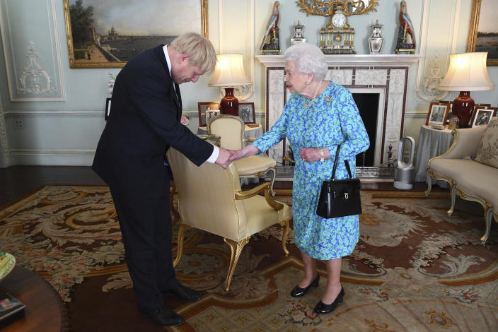 FILE - In this Wednesday July 24, 2019 file photo Britain's Queen Elizabeth II welcomes newly elected leader of the Conservative party Boris Johnson during an audience at Buckingham Palace, London, where she invited him to become Prime Minister and form a new government. (Victoria Jones/Pool via AP, File)