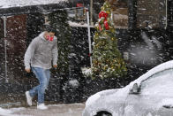 A man runs through heavy snow, Saturday, Dec. 5, 2020, downtown in Marlborough, Mass. The northeastern United States is seeing the first big snowstorm of the season. (AP Photo/Bill Sikes)