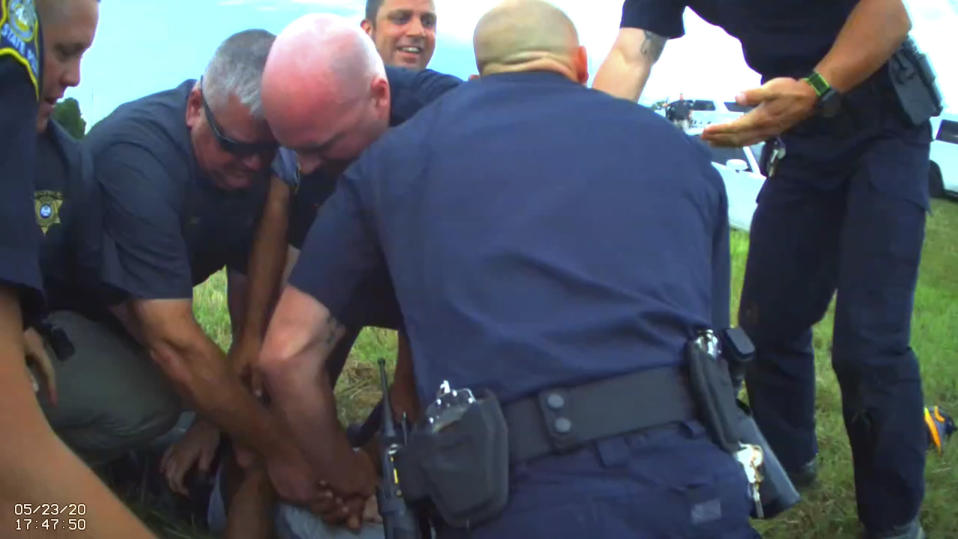 In this Saturday, May 23, 2020 image from Franklin Parish Sheriff's Office body camera video, law enforcement officers restrain motorist Antonio Harris, bottom center, on the side of a road after a high speed chase in Franklin Parish, La. (Aaron Touchet/Franklin Parish Sheriff's Office via AP)