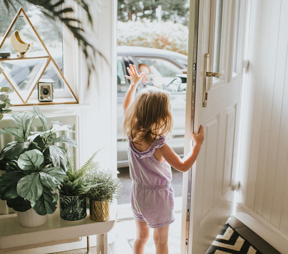 Cute little girl waving out the door in a sunny hallway.