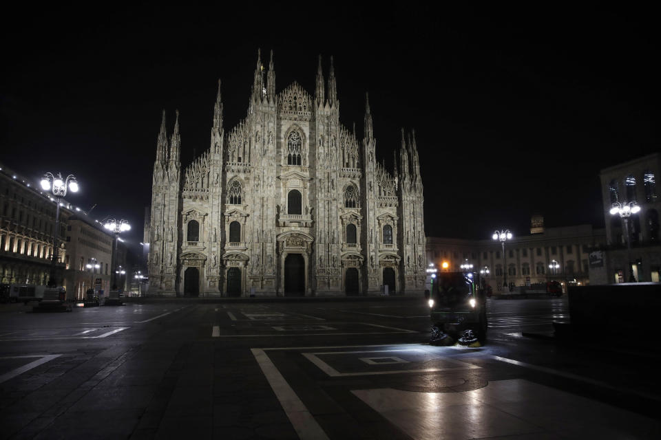 A street cleaning vehicle washes the square in front of the Duomo gothic cathedral, in Milan, northern Italy, early Sunday, Oct. 25, 2020. Since the 11 p.m.-5 a.m. curfew took effect last Thursday, people can only move around during those hours for reasons of work, health or necessity. (AP Photo/Luca Bruno)