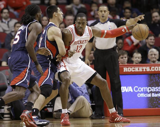 Houston Rockets' Dwight Howard (12) pushes against Atlanta Hawks defenders Gustavo Ayon, center, and DeMarre Carroll (5) in the first half of an NBA basketball game Wednesday, Nov. 27, 2013, in Houston. (AP Photo/Pat Sullivan)
