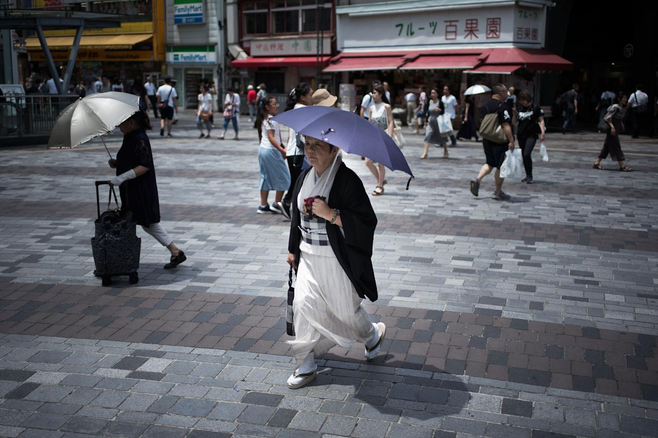 <p>A woman holds an umbrella as she walks along a street in Tokyo on July 23, 2018, as Japan suffers from a heatwave. (Photo: Martin Bureau/AFP/Getty Images) </p>