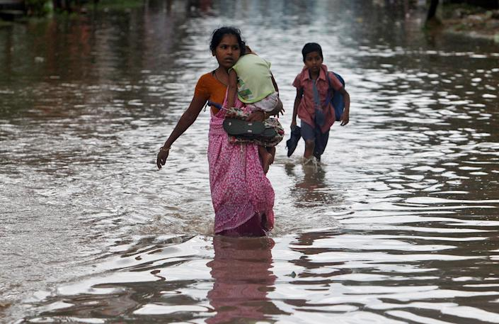 <p>A schoolboy and a woman carrying a child wade through a flooded road after heavy rains in Agartala, India, June 1, 2017. (Jayanta Dey/Reuters) </p>