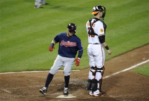 Cleveland Indians' Nick Swisher, left, steps on home plate against Baltimore Orioles catcher Matt Wieters, right, to score on a single by Michael Brantley during the sixth inning of a baseball game, Monday, June 24, 2013, in Baltimore. The Indians won 5-2. (AP Photo/Nick Wass)