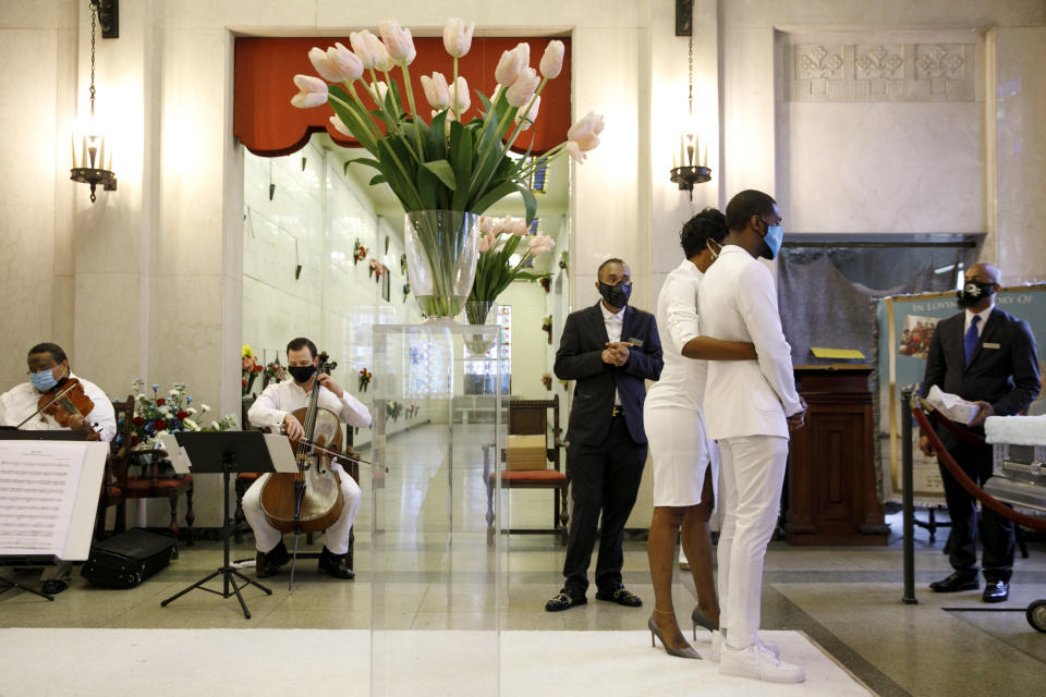 As a masked string quartet plays, Compassion and Serenity Funeral Home Administrator Dani Skinner, center, is present to assist mourners at the viewing of Joanne Paylor, 62, of southwest Washington, during her funeral in Suitland-Silver Hill, Md., Sunday, May 3, 2020. The original funeral for Paylor, who the family believes died of a heart attack, was delayed for close to two months while her family hoped social distancing guidelines would be lifted. When it became clear it would not they decided to proceed and were able to arrange a viewing with only ten people cycling inside at a time from 6 feet apart, and an outdoor service. Despite not having died from coronavirus, almost every aspect of her funeral has been impacted by the pandemic. (AP Photo/Jacquelyn Martin)