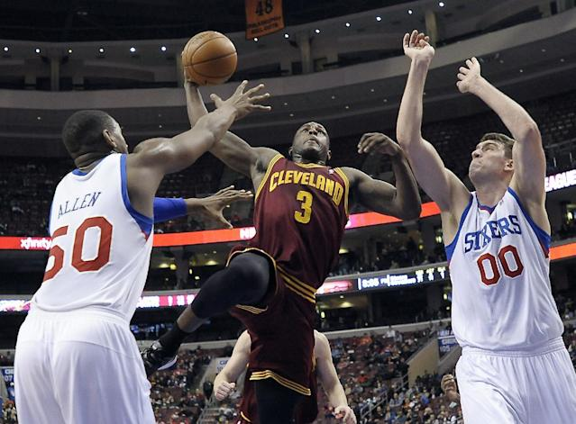 Cleveland Cavaliers' Dion Waiters (3) goes up for a dunk over Philadelphia 76ers' Lavoy Allen (50) and Spencer Hawes (00) during the first half of an NBA basketball game, Tuesday, Feb. 18, 2014, in Philadelphia. (AP Photo/Michael Perez)
