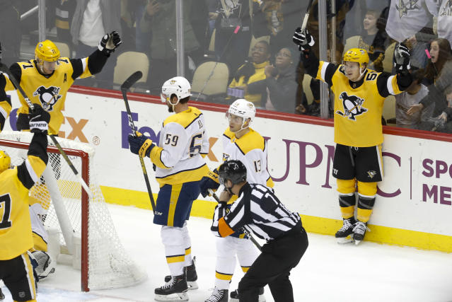 Pittsburgh Penguins' Jake Guentzel (59) celebrates after scoring as Nashville Predators' Roman Josi (59) and Nick Bonino skate by during the third period of an NHL hockey game Saturday, Dec. 28, 2019, in Pittsburgh. The goal was reviewed and confirmed. The Penguins won 6-4. (AP Photo/Keith Srakocic)