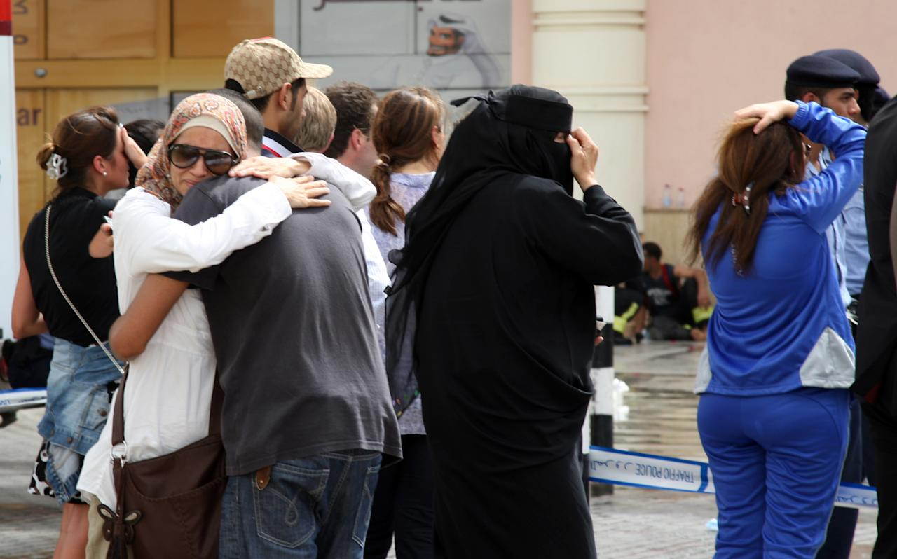 Family members of victims of a fire react in grief after a fire took hold of the Villaggio Mall, in Doha's west end, in the Qatari capital of Doha Monday May 28, 2012. Qatar's Interior Ministry said 13 children were among 19 people killed in a fire that broke out at one of the Gulf state's fanciest shopping mall on Monday. The Villaggio opened in 2006 and is one of Qatar's most popular shopping and amusement destinations. It includes an ice skating rink and indoor Venice-style gondola rides. (AP Photo/Osama Faisal)