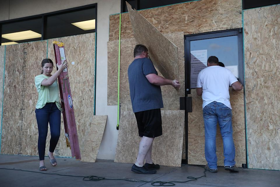 (L-R) Lacey Buller, Tyler Arnold, and Mike Buller work on placing plywood over the windows of their business before the arrival of Hurricane Laura on August 25, 2020, in Lake Charles, Louisiana. (Photo by Joe Raedle/Getty Images)