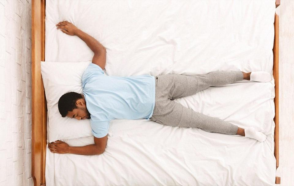 African american millennial guy sleeping, lying on stomach in bed