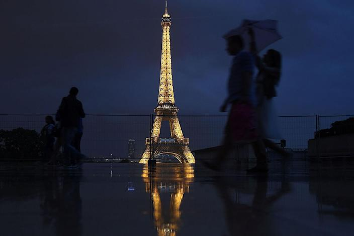 <p>People with umbrellas walk at the Palais de Chaillot near the illuminated Eiffel Tower in Paris on July 13, 2017, as President Donald Trump and French President Emmanuel Macron attend a dinner with their wives at the restaurant 'Le Jules Verne' on the tower's second floor. (Photo: Jean-Sebastien Evrard/AFP/Getty Images) </p>