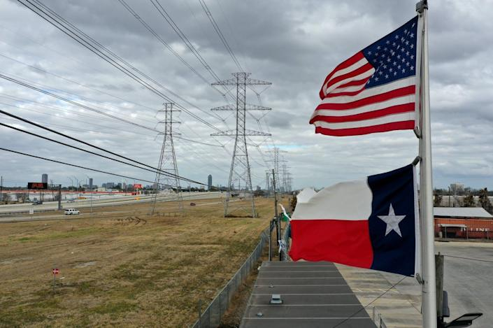 """<span class=""""caption"""">Power to the people, but it will cost you.</span> <span class=""""attribution""""><a class=""""link rapid-noclick-resp"""" href=""""https://www.gettyimages.com/detail/news-photo/the-u-s-and-texas-flags-fly-in-front-of-high-voltage-news-photo/1303397476?adppopup=true"""" rel=""""nofollow noopener"""" target=""""_blank"""" data-ylk=""""slk:Justin Sullivan/Getty Images"""">Justin Sullivan/Getty Images</a></span>"""