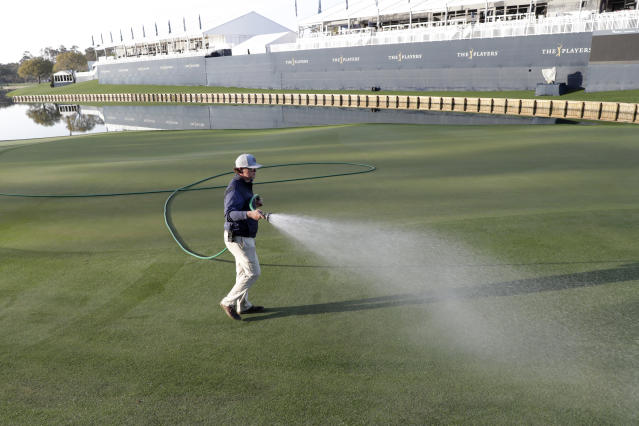 A grounds crew worker waters the 18th green after the PGA tour canceled the rest of The Players Championship golf tournament as a result of the coronavirus pandemic, Friday, March 13, 2020, in Ponte Vedra Beach, Fla. (AP Photo/Lynne Sladky)