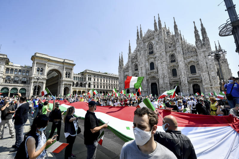 People hold a giant Italian flag as they stage an anti-government protest set by the center-right opposition, in front of Milan gothic cathedral, Italy, Tuesday, June 2, 2020 on the day marking the 74th anniversary of the Italian Republic. (Claudio Furlan/LaPresse via AP)