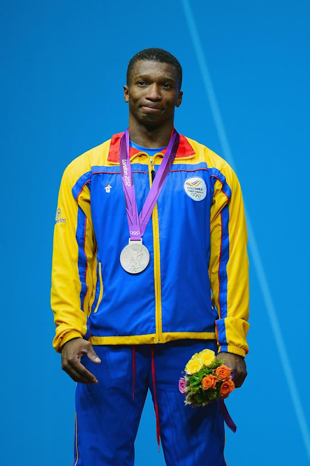 LONDON, ENGLAND - JULY 30: Oscar Albeiro Figueroa Mosquera of Colombia celebrates with the silver medal on the podium after the Men's 62kg Weightlifting on Day 3 of the London 2012 Olympic Games at ExCeL on July 30, 2012 in London, England. (Photo by Lars Baron/Getty Images)