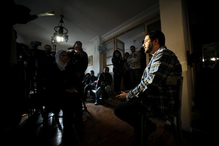 Egyptian blogger and activist Alaa Abdel Fattah (R) gives television interviews in his house in Cairo on December 26, 2011