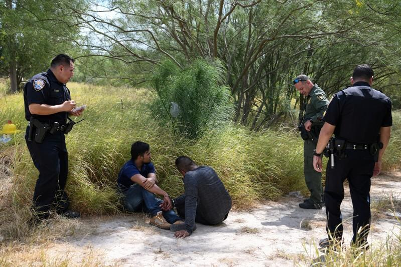FILE PHOTO: Migrant men sit on the ground after being detained by law enforcement for illegally crossing the Rio Grande and attempting to evade capture in Hidalgo